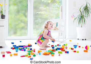 Curly laughing toddler girl playing with colorful blocks