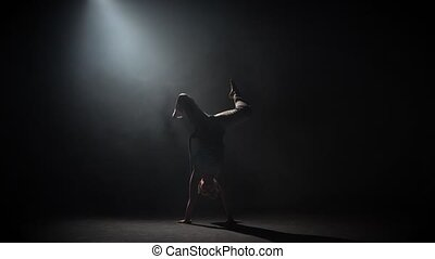 Curly maiden practicing capoeira in darkness against...