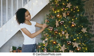 Curly mixed race girl decorating Christmas tree at home...
