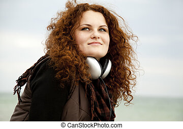 Curly red-haired girl with headphones.
