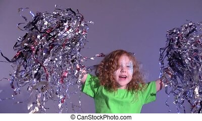 Curly redheaded girl jumping with tinsel on gray background...