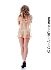 Curly slim girl posing in beige erotic negligee