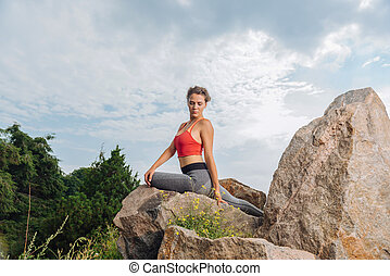Curly slim woman sitting on rock while resting after workout