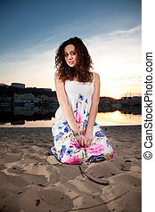 Curly woman in dress sitting on knees at beach