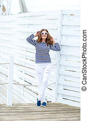 curly woman on a white background in a stylish white jeans.