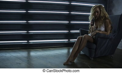 Curly woman sits in armchair and smokes electronic cigarette