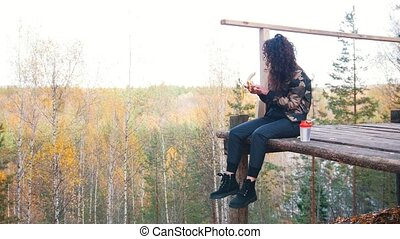 Curly woman sits on a altitude platform and eats banana....