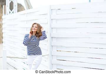 curly woman take a photo at wooden background in a stylish white jeans.