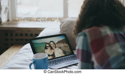 Curly young woman having online video chat with friends using laptop camera while lying on bed
