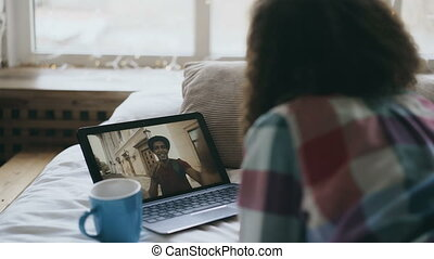 Curly young woman having online video chat with friend using...