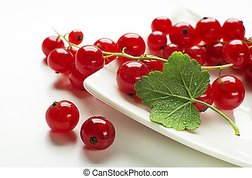 Fresh red currant berries with leaf on wooden background close up