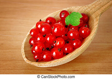 currant in wooden spoon - currant berries with green leaf in...