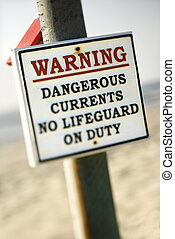 Current warning sign. - Warning sign on post at the beach...