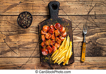 Curry wurst Sausages with French fries on a wooden board. wooden background. Top view