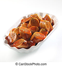 Bowl of sliced spicy Currywurst and tomato ketchup over white, close up high angle view
