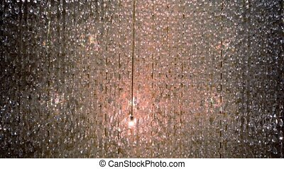 Curtain made of glass beads at background of tiled wall