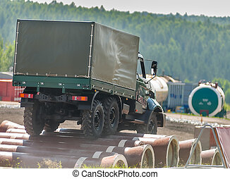 Curtain sided truck moves on obstacle from pipes