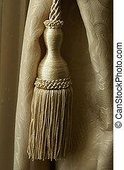 A clsoeup shot of an elegant curtain tassel.