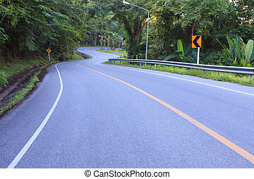 curve of asphalt road in mountain high ways and jungle beside us