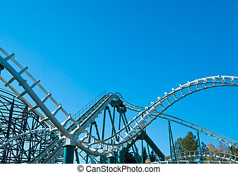 curved roller coaster tracks at the clear blue sky