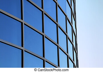 Curved exterior windows of a commercial office building reflecting a blue sky