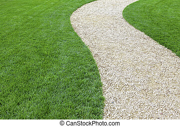 Curved garden stone path with fresh green cultivated lawn