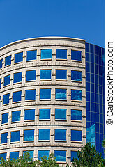 Curved Office with Clouds Reflected in Blue Glass