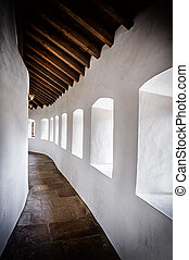 Curved passage in ancient castle - Curved passage with white...