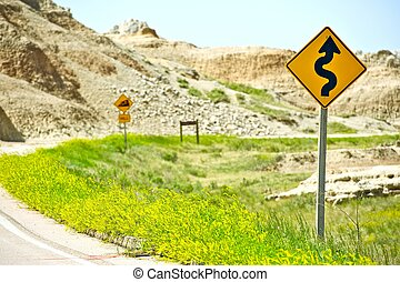 Curved Badlands Road and Warning Signs.