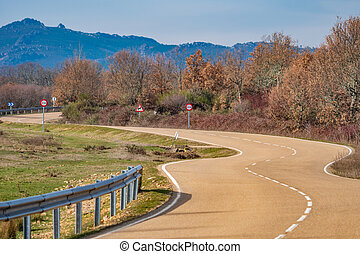 Curved road towards the mountain range, winter time