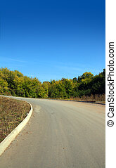 curved road uphill under clear blue sky