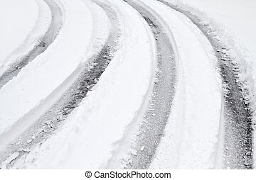 Multiple curved vehicle tire tracks on a snow covered road one wintry day in January. Weather conditions such as this create a number of hazardous conditions for drivers on the asphalt roadways.