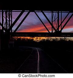 Curving bike trail under a bridge at sunset