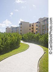 Curving Sidewalk Through Tropical Resort - A concrete...