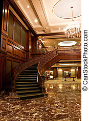 A carpeted curved staircase in a brightly lit tradional lobby