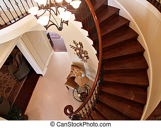 Interior view of a foyer with curving staircase, tiled floors and furniture
