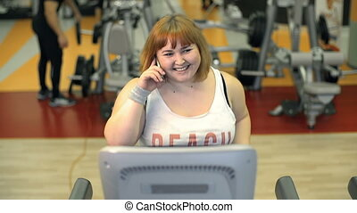 Curvy Cutie - Front view of stout lady running on gym...