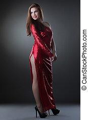 Curvy smiling woman posing in red long dress