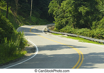 Winding, curvy road in the mountains near Cabin Creek, WV on a sunny morning in the summer.