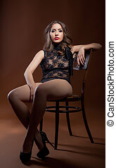 Curvy woman posing in lingerie sitting on chair