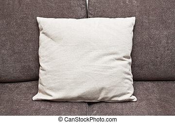 An off-white cushion on a brown sofa