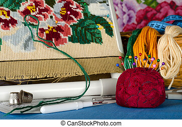 Cushion for pins and a set of cross stitching