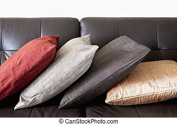 Cushions on leather sofa - Four colorful cushions on dark ...