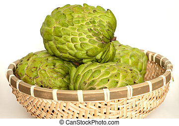 Custard apples in a bamboo basket isolated on white...