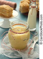 Custard cream in glass jar on blue wooden background