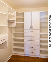 Custom Closet - Custom white wood cabinetry in a walk in...