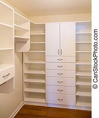 Custom Closet - Custom white wood cabinetry in a walk in...
