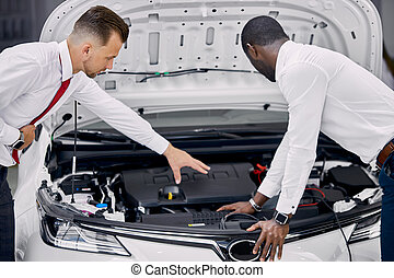 customer and salesman opened the car hood and discuss all ...