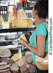 Customer Buying Cheese In Grocery Shop