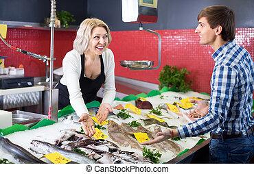 Customer buying fish in shop.